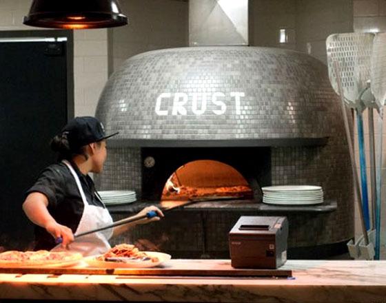 本場のピザ窯にクラストを投入